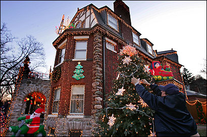 Dominic Luberto adjusted some of the 250,000 lights that decorate his house yesterday. NStar has visited his house twice to adjust his electricity.