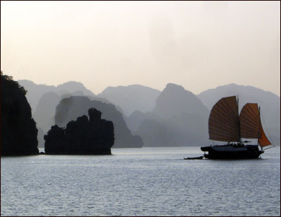 A sampan sails through dusk on Halong Bay.