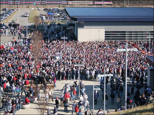 Crowds gathered in unseasonably warm weather beneath the west gates of Gillette Stadium.