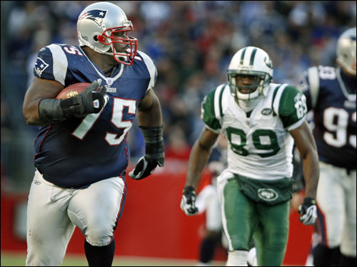 ...Patriots defensive lineman Vince Wilfork (75) rumbled down the field with Jets wide receiver Jerricho Cotchery (89) in pursuit after Wilfork recovered a Chad Pennington fumble late in the third quarter. Wilfolk ran it back 31 yards to set up a New England field goal.