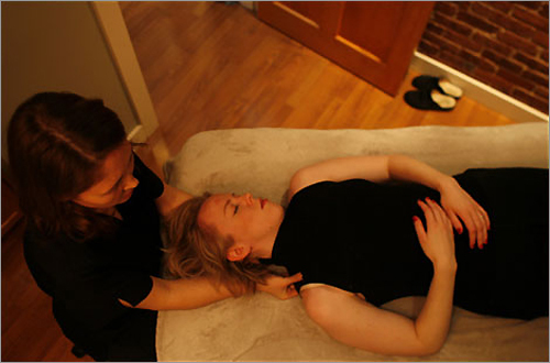 Heidi Fischbach, left, massages Rachel Hagadorn at the Carriage House Salon. Customers enjoy a comfortable massage table and soft music during the salon's massages.