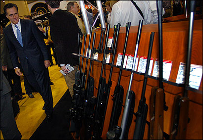 Presidential prospect Mitt Romney checked out a display Friday during his NRA-guided tour of a sprawling gun trade show in Orlando, Fla.