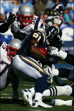 LaDainian Tomlinson (21) was tackled by Vince Wilfork (left) after a gain of three yards.
