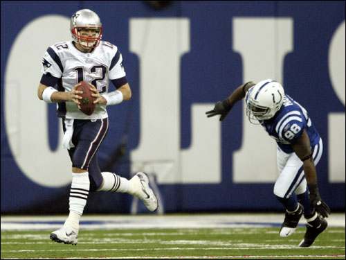 Tom Brady rolled out of the pocket while being pursued by Robert Mathis (right).