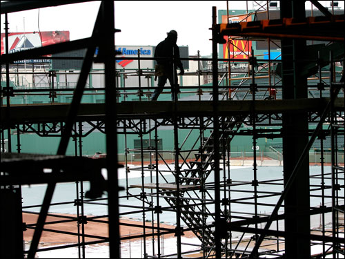 A worker walked along scaffolding along the first base line at Fenway Park on Wednesday.