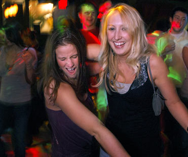 Eulalia Zukas, left, of South Portland, Maine and Erin Phelan of Tewksbury, Mass. danced with each other and college friends at 51 Wharf in the Old Port District in Portland, Maine.