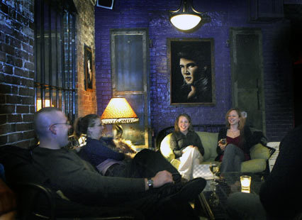 Elvis Presley paintings add to the ambiance at The Wine Bar as from left, Tim Farwell and his wife Sarah Farwell, of Gorham, Maine chat with Heidi Dorrity of Hampden, Maine and Tim's sister Katie Farwell of Portland, Maine. 'I love it, it's different,' said Katie Farwelli of this resataurant and bar in the Old Port District in Portland, Maine.