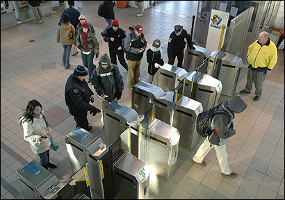 MBTA personnel helped students through the new turnstiles at the JFK/UMass stop on the Red Line, after a hitch with the student fare CharlieCards.