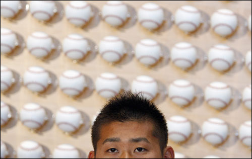 Matsuzaka answered questions in front of a wall of baseballs.
