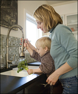 Megan Hyatt and 2-year-old Kaden in the kitchen, where the tiles are made from recycled glass and the counter is recycled stone.