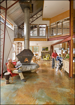 David Hall sat by the hearth, a massive boulder, in his home's living area, where south-facing windows provide passive solar heat and a sunfueled radiant system warms the concrete floor.