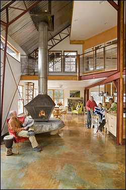 EXTREME RECYCLING Lisa Dorval and David Hall's Newbury house is built in large part with materials salvaged from other buildings and construction projects. The concrete floors are warmed by a solar-powered thermal system. The hearth is a massive boulder, the ceiling is corrugated metal, and the I-beams were recovered from a boat-building shop. David Hall, left, bought the used 16-inch galvanized steel stove pipe at a fraction of the cost of a new one. The couple's son Emmett sits at the kitchen counter with his mother and grandfather, Romeo Dorval.