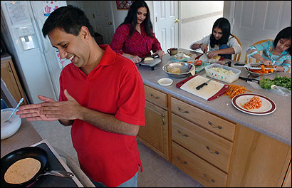 Vijay Kumar cooked chapati bread as his wife, Vanitha, and daughters (from left) Apoorva and Niru prepared the other ingredients. The family's last name used to be Vijaykumar.