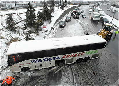 A Fung Wah bus crashed near the Allston-Brighton tollbooths on the Massachusetts Turnpike in slushy conditions yesterday, and the driver for the troubled line was cited for speeding, negligence, false records, and an equipment violation.