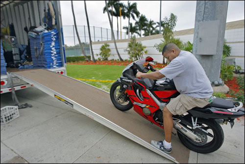 Clubhouse attendant Kenyatta Gomez rolled his motorcycle, which made the trip south on the truck, down the ramp.