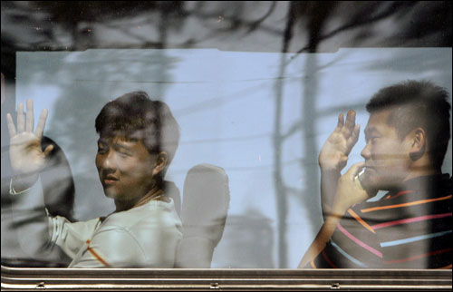 Red Sox pitchers Hideki Okajima (left) and Daisuke Matsuzaka waved from the team bus as they departed for their physicals.