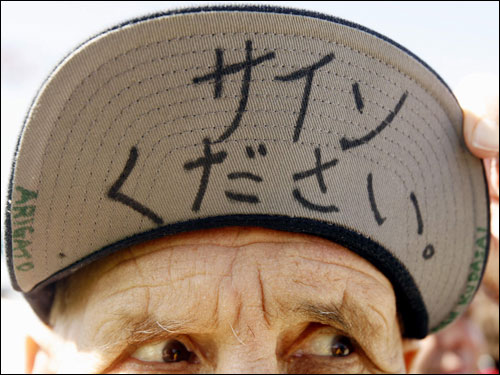 Red Sox fan Joe McGrady showed off the brim of his cap, on which he has written 'Please sign' in Japanese, in an attempt to get an autograph from Red Sox pitcher Daisuke Matsuzaka.