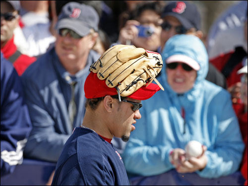 Manny Delcarmen walked the field with his glove on his head.