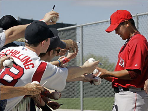 Matsuzaka (right) signed autographs for fans at the Red Sox spring training facility.