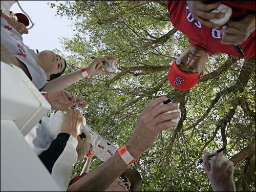 Hideki Okajima signed autographs during spring training workouts.