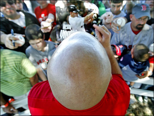 No, space aliens have not invaded spring training, it's actually Red Sox first baseman Kevin Youkilis, who has a shaved head, signing a poster of himself as he obliged fans after his workout Tuesday.