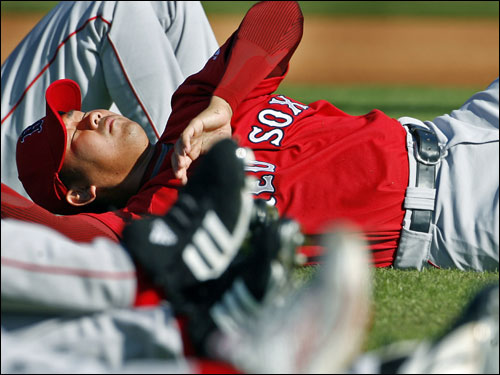 Daisuke Matsuzaka is surrounded by the legs of teammates as he participated in morning stretching drills Tuesday.