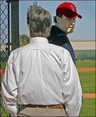 Curt Schilling (right) looked back at Red Sox owner John Henry as the two walked onto the field where Schilling was preparing to practice.