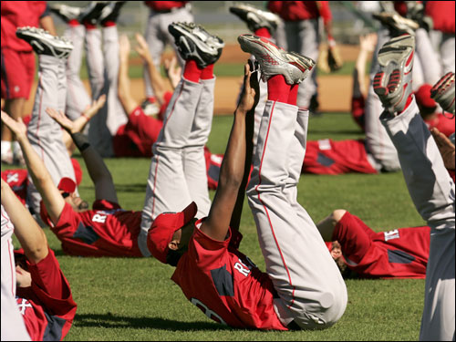Red Sox players, including Devern Hansack (center), stretched out.