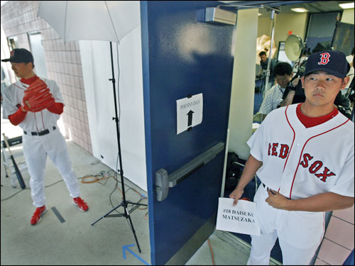 Today was the annual 'Photo Day' at spring training, where the players dress in their home white uniforms and pose for baseball cards, ballpark programs, wire service files and various other head shots. Here, Dice-K waited his turn while Hideki Okajima got his picture taken.