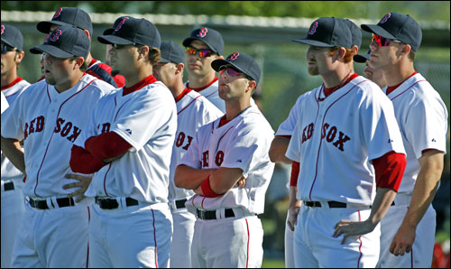 Red Sox players stood and listened to instructions from a coach.