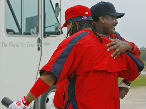 Red Sox left fielder Manny Ramirez (left) got a hug from another legendary Boston left fielder, Jim Rice (right), after Ramirez surprised everyone by showing up in camp before he said he would (note the words on the delivery truck in the background).