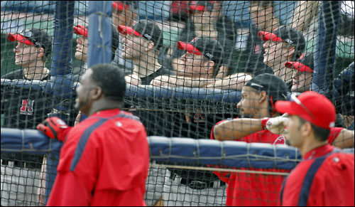 Northeastern University baseball players got to admire the flight of a Manny Ramirez batting practice shot before their game at City of Palms Park. David Ortiz and Mike Lowell are in the foreground.
