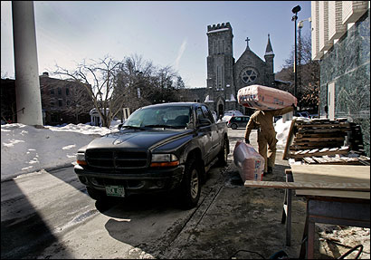Tod Hill carried insulation to protect doors at the Federal Building in Montpelier. At right, Main Street was flooded in downtown Montpelier in 1992, causing more than $5 million in damage.