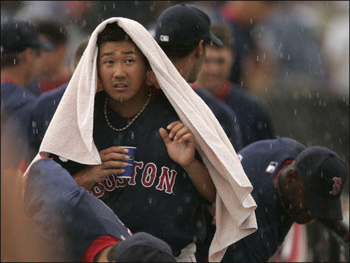 Red Sox pitcher Daisuke Matsuzaka took cover under a towel before heading off the field for a rain delay in the third inning against the Los Angeles Dodgers. The game was eventually called.