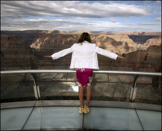 A tourist held her arms up to feel the wind coming up from the Grand Canyon on March 20 as she stood on the Skywalk. She wore cloth booties to keep dirt off of the glass walkway. The $30 million glass-bottomed walkway juts out 70 feet from the rim at an elevation of 4,000 feet above the Colorado River.