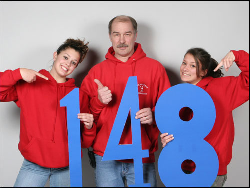 Members of the Barnstable gymnastics team -- (left to right) Leah Pacheco, Duncan Chase and Allison Szatek -- pose with the number 148 after the team set a state record by scoring 148.125 during the state finals.