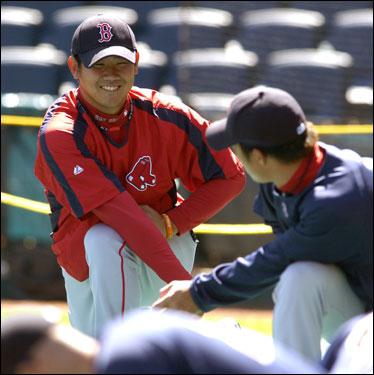 Daisuke Matsuzaka (left) smiled at teammate Hideki Okajima while warming up.