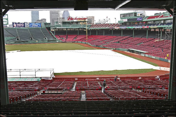 Workers walk through the stands at Fenway Park on Wednesday.