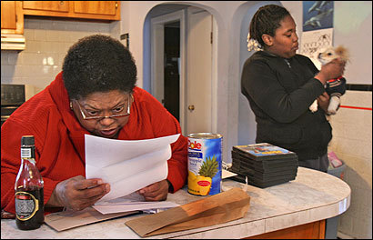 Patricia Jones examined a water bill in her Quincy home. Granddaughter Tiare Jones is at right.