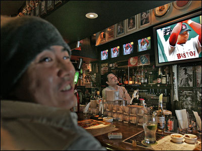 At the Brain Buster sports bar in Tokyo Japan, Japanese baseball fans including the bartender Kyozo Watanabe (center) watched Red Sox pitcher Daisuke Matsuzaka pitch against Kansas City. On the left is Mahiro Ochi, a customer at the bar.