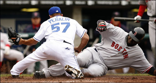 David Ortiz (right) slid safely into home plate past the tag of Royals pitcher Joel Peralta in the eighth inning.