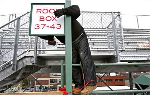 'Spring signifies rebirth and hope, and nowhere does hope blossom more fervently each spring as it does in Fenway Park,' writes Globe correspondent Linda Laban. Worker Sergio Mallea installed a sign for new roof box seats at Fenway Park on Wednesday.