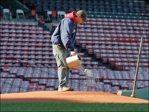 A worker gets the pitcher's mound ready for another season at Fenway Park.