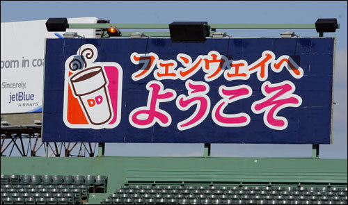 A new Dunkin' Donuts billboard in right field is written in Japanese. It says 'Welcome to Fenway Park.'
