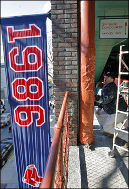 Painter Dan Mulkern put some finishing touches on a pole in the upper third base side grandstand, with Yawkey Way visible at left.