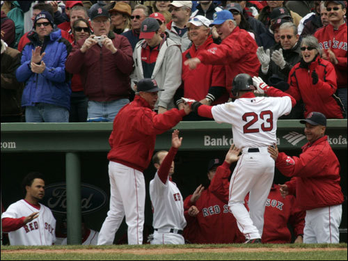 Julio Lugo was congratulated by manager Terry Francona (right) and the rest of the team after scoring the first run of the season at Fenway Park.