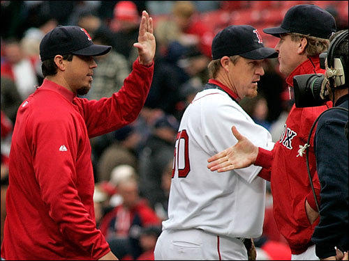 Red Sox starting pitcher Josh Beckett got a high five from Curt Schilling (right) after the Red Sox defeated the Mariners 14-3 in the home opener.