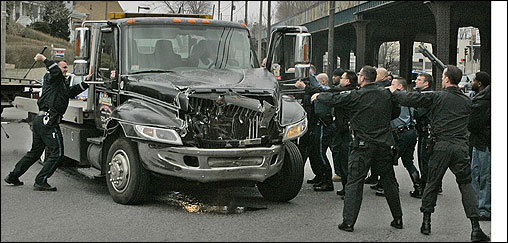 Police officers surrounded a stolen flatbed tow truck on Columbia Road in Dorchester Tuesday morning after its driver allegedly led them on a chase through the area. One officer prepared to break the passenger-side window while others tried to force the suspect out of the truck.