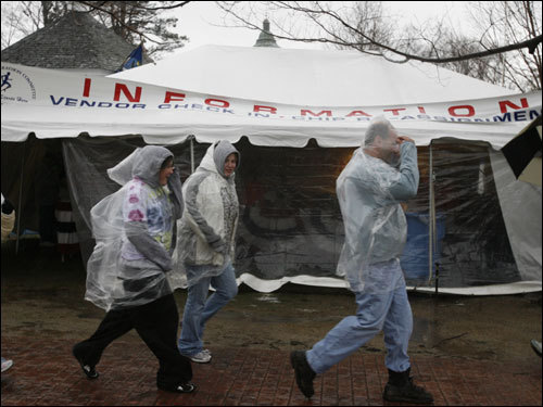 Runners tried to stay dry in Hopkinton before the race.
