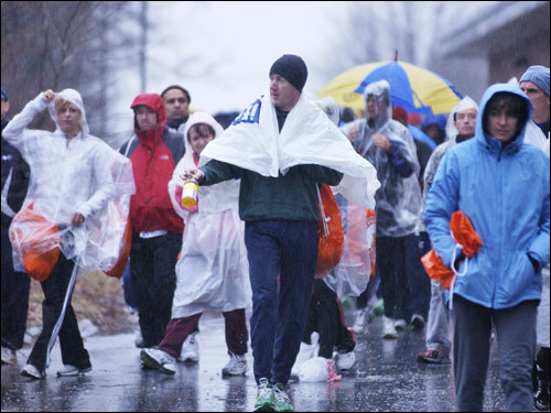 Runners walked through the pouring rain in Athlete's Village prior to the start of the marathon.